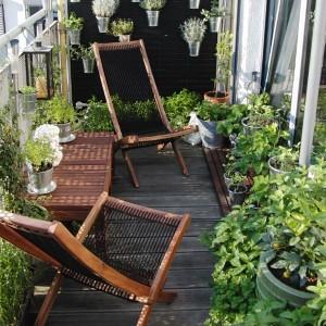 petit balcon aménagé avec chaises et table en bois