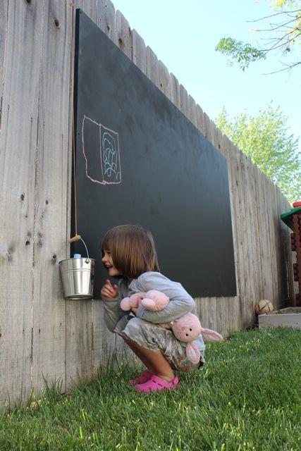 une fillette contre un tableau noir à l'extérieur