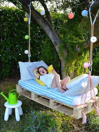 un enfant se repose sur une balancelle en palettes DIY