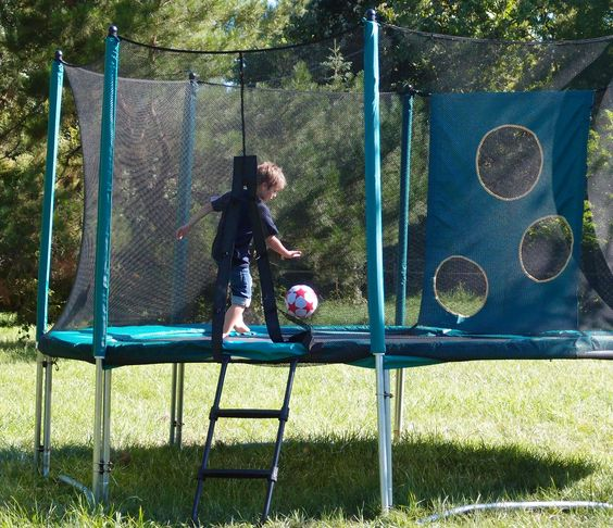 un enfant joue au foot sur un trampoline