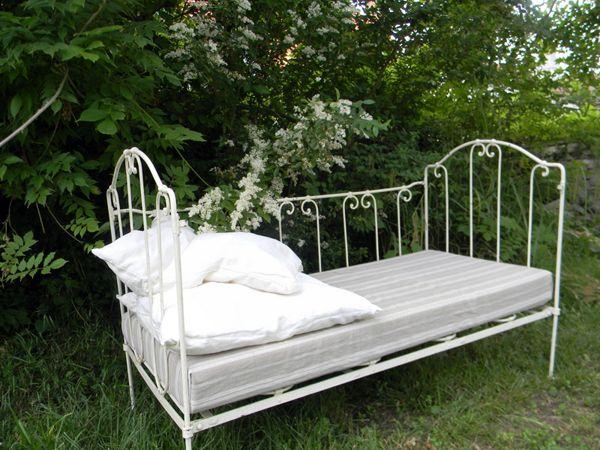 Un lit en fer blanc placé sous les arbres