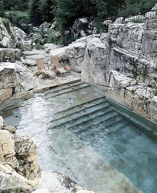 une terrasse avec piscine taillée dans la pierre de la montagne