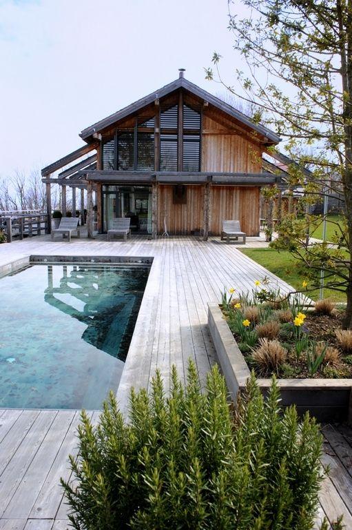 une terrasse en bois vieilli de style nordique avec grande piscine creusée