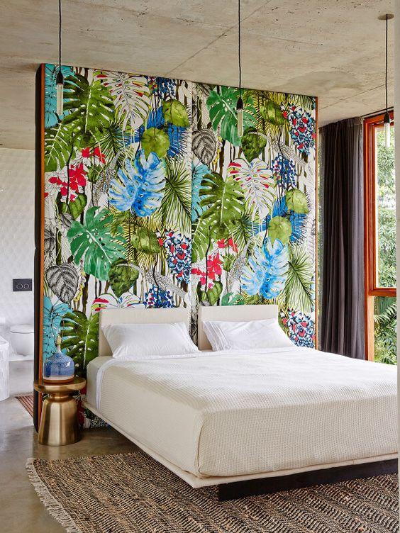 Une chambre avec une tête de lit en papier peint