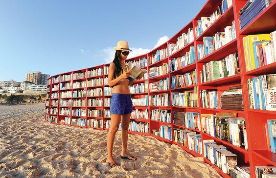 Une bibliothèque au bord de la mer : des rayonnages de livres sur la plage